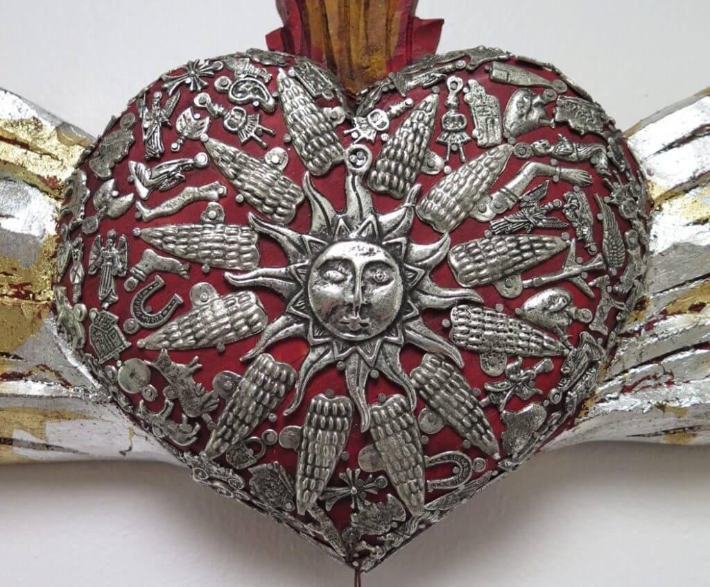 Milagros hand made onto a Sacred Heart.