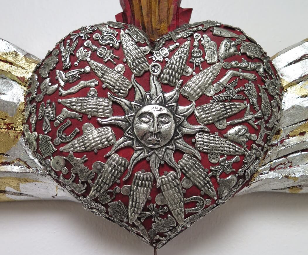 Milagros hand made onto a Sacred Heart.